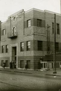 Quelques personnes sont debout devant l'entrée d'un édifice de trois étages.