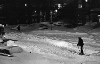 Un homme en ski au milieu d'une rue enneigée