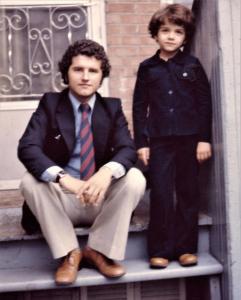 Photo couleur d'un jeune homme assis dans les marches de la maison familiale et son jeune frère debout à ses côtés.