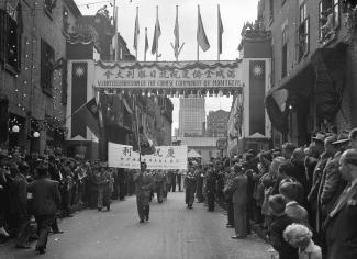 """Foule qui célèbre dans le Quartier chinois. On peut lire sur une banderole \""""V-J Day celebration by the Chinese community of Montreal\""""."""