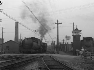 La locomotive et le wagon de queue passent sur la voie ferrée devant Gabrielle Roy.