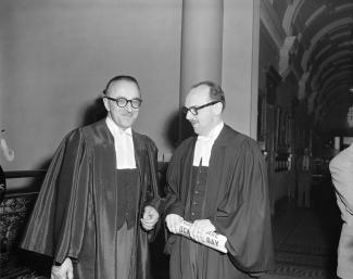 Deux hommes à lunettes portant la toge d'avocat se tiennent debout dans une salle non identifiée. L'homme de droite tient un journal dans ses mains.