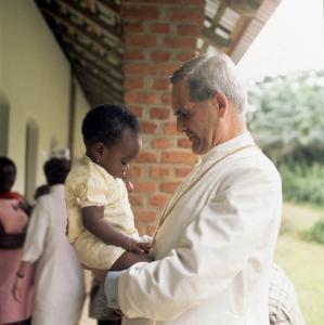 Photographie du cardinal Léger tenant une enfant.dans un centre.