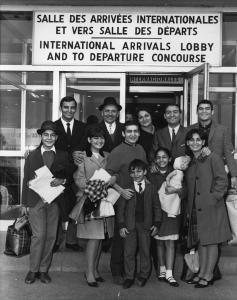 Onze personnes souriants, debouts à l'aéroport à la salle des arrivées internationales.