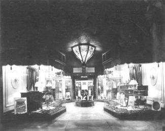 Cette pièce montre des produits Victor vendus chez le détaillant situé au 757-755, rue Sainte-Catherine Ouest, à Montréal. La vitrine contient un Victrola 2-55, des feuilles de musique, des disques du Film The Broadway Melody et une figurine de Nipper.