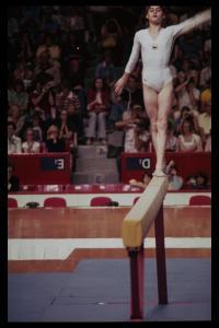 Photographie de la jeune fille en équilibre debout sur une poutre.