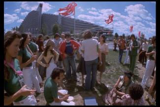 Une foule de personnes bavardent et jouent de la musique devant une pyramide du village olympique