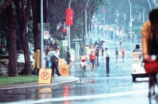 Photographie de deux athlètes courant sous la pluie dans le circuit de course qui passe par les rues.