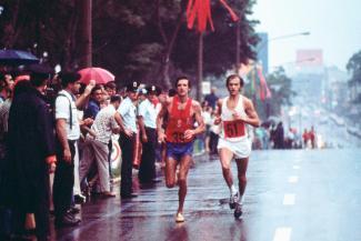 Photographie de deux athlètes courant dans la rue sous la pluie, avec une foule alignée sur le côté.