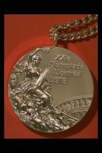 Photographie d'une médaille avec chaîne, avec mention «XXIe Olympiade Montréal 1976».