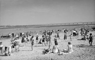 Plage avec plusieurs dizaines de baigneurs de tous âges, dont certains sont dans l'eau du fleuve, avec au loin le pont Victoria.