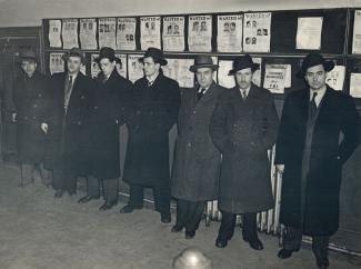 Photo noir et blanc de sept enquêteurs de police devant un babillard de personnes recherchées.