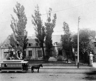 Vue sur le Château Ramezay bordé d'arbres, et sur la rue Notre-Dame avec un tramway tiré par un cheval.