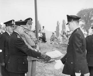 Un policier tend la main à un jeune policier fraîchement diplômé. D'autres policiers sont autour d'eux en plein air dans un parc.