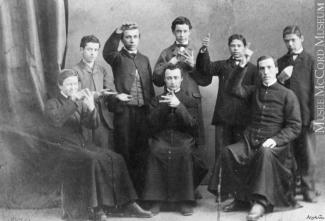 Deux hommes en habits religieux entourés de six enfants.