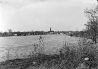 Rivière bordée par des berges couvertes de quelques arbres et arbustes avec au loin un barrage hydroélectrique et divers autres bâtiments.