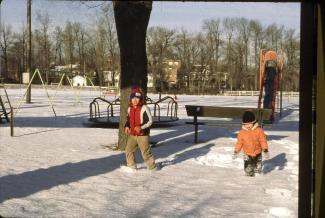 Deux enfants jouent dans la neige dans un parc