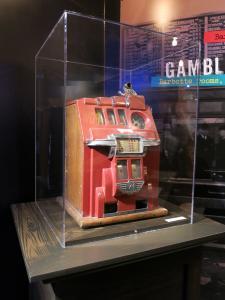 Machine à sous rouge avec détails chromés dans une vitrine dans une salle d'exposition.