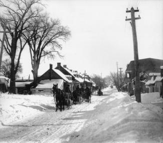 Photographie en noir et blanc représentant une série de petites maisons bordant un chemin de campagne, recouvert de neige.