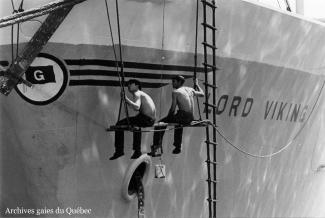 Photo de marins peignant la coque d'un bateau.