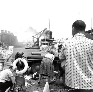 Photo de peintres installés le long d'un quai du port de Montréal.
