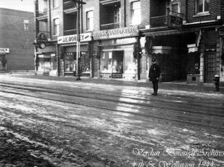 Photographie noir et blanc de la rue Wellington au premier plan et, en arrière-plan, du commerce Tousignant & Frères. Un policier se tient debout dans la rue sur la droite.