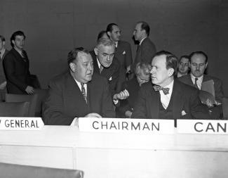 Deux hommes attablés dans une salle d'assemblée discutent.
