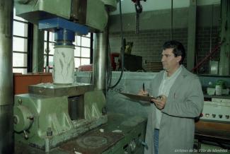 Un homme observe une machine dans un atelier.