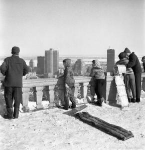 Scène d'hiver sur le belvédère du mont Royal. Des enfants et des adultes admirent la vue sur le centre-ville.