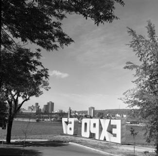 Les lettres « Expo 67 » sont installées, suite aux cérémonies du début des travaux, sur l'île Sainte-Hélène, près du fort.