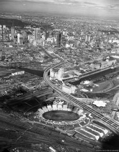 Vue aérienne de l'autoroute Bonaventure parmi le paysage urbain montréalais, vue du sud. On aperçoit l'usine Five Roses au centre ainsi que le mont Royal en haut à gauche.