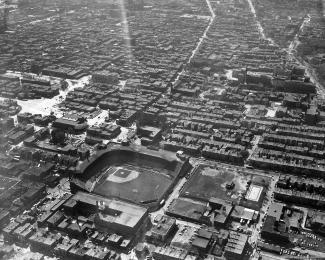 Vue aérienne en noir et blanc montrant un stade de baseball dans une ville densément bâtie.