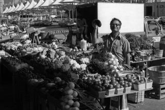 Un commerçant derrière ses étals de légumes au marché montre une aubergine.