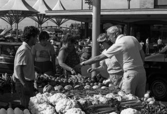 Des gens pointent des légumes autour d'un étal au marché.