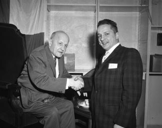Albert J. Giroux (assis) serrant la main du photographe Jean-Paul Gill lors d'une fête pour la retraite de M. Giroux.