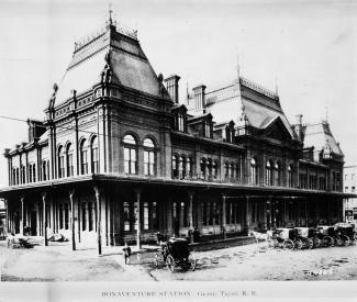 Vue extérieure de la gare avec des voitures tirées par des chevaux
