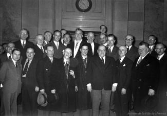 Photographie d'un groupe d'employés et de conseillers municipaux dans le hall d'honneur.