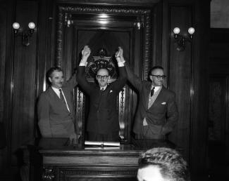 Photo noir et blanc montrant trois hommes les bras en l'air en signe de victoire.
