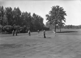Photographie noir et blanc de six golfeurs sur un terrain.