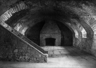 Photographie d'une pièce du fort de l'île Sainte-Hélène. On y voit un escalier en pierre et un foyer.