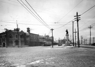Photo noir et blanc à l'angle des voies Notre-Dame et De Lorimier. On voit la prison en arrière-plan.