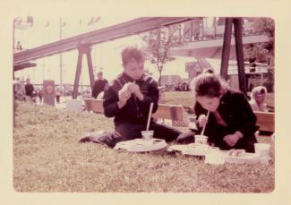 Deux enfants mangent un repas de casse-croûte assis sur la pelouse à Expo 67