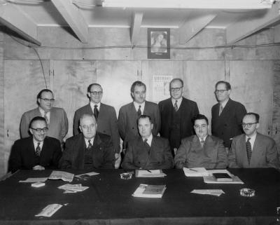 Photographie en noir et blanc d'un groupe d'hommes se tenant derrière une table de travail. Ils portent tous un complet-cravate.