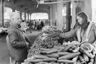 Photo en noir et blanc d'un homme âgé se tient devant un kiosque de légumes dans un marché.