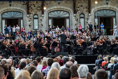 Un orchestre joue à l'extérieur, devant un édifice de pierre, et une foule assise écoute.