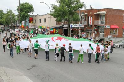 Une foule tenant un grand drapeau de l'Algérie dans le Petit Maghreb.