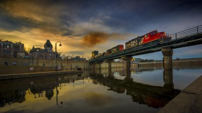 Photo couleur prise dans le Vieux-Port sur la berge devant le silo no 5 et présente un ciel de début de soirée coloré. Un train du CN passe sur le pont qui relie le Vieux-Port et le quai.