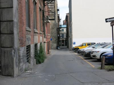 La ruelle Saint-Éloi, très étroite, avec un stationnement à droite et les façades de bâtiments à gauche.