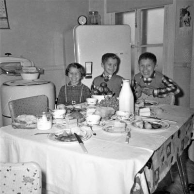 Photo en noir et blanc de trois enfants souriant dans une cuisine avec un réfrigérateur et une machine à laver avec essoreuse. Devant eux, une table bien remplie.