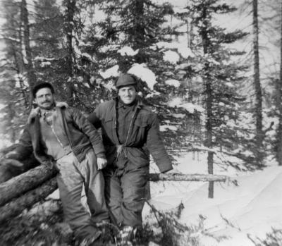 Photographie de deux hommes appuyés sur des billots de bois, dans la forêt en hiver.